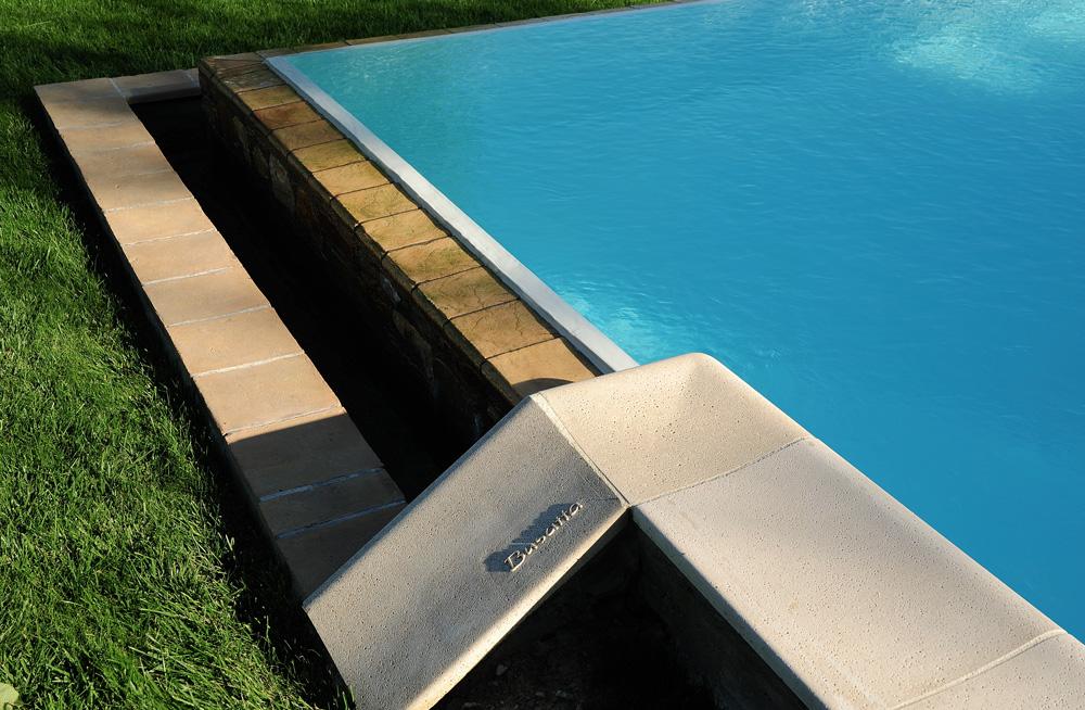 Dettaglio piscina a sfioro con bordo in pietra MsPiscine